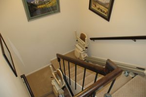 Two straight stairlifts on a staircase with a landing. The rider transfers from one stairlift to the next.